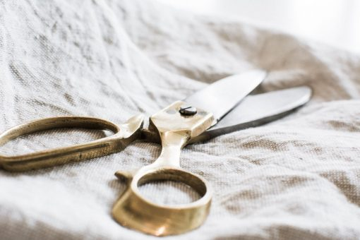Brass scissors on linen